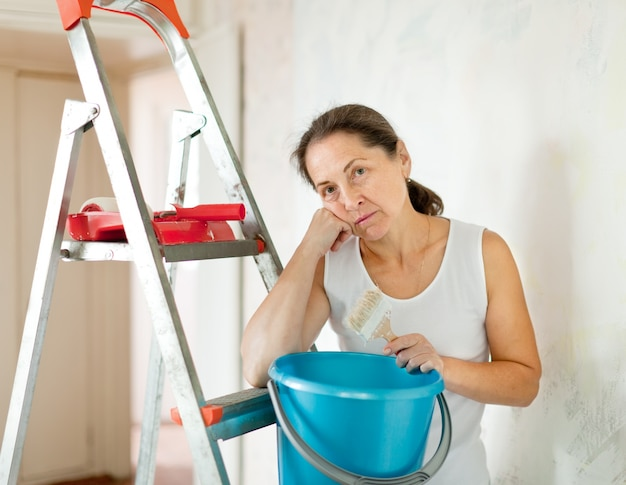 Mature woman makes repairs at home
