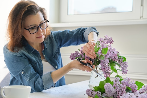 Mature woman making bouquet of lilac branches at home at table in living room