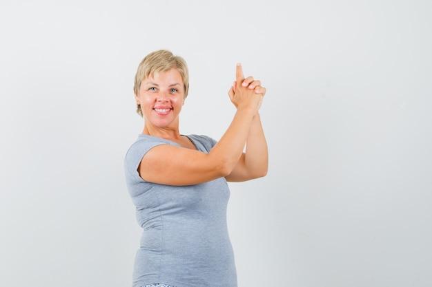 회색 티셔츠에 손가락 권총 기호를 만들고 자신감을 찾는 성숙한 여인