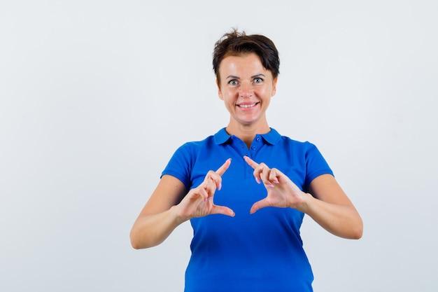 青いtシャツでフレームジェスチャーをして幸せそうに見える成熟した女性。正面図。