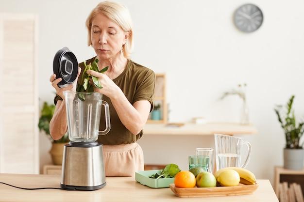 キッチンに立っている間、ブレンダーを使用してほうれん草と果物から健康的なカクテルを作る成熟した女性