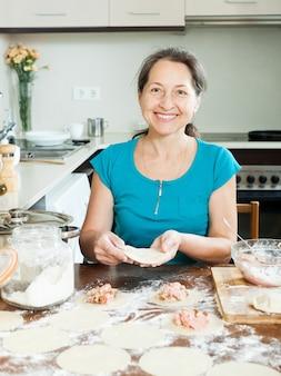 Mature woman making meat dumplings