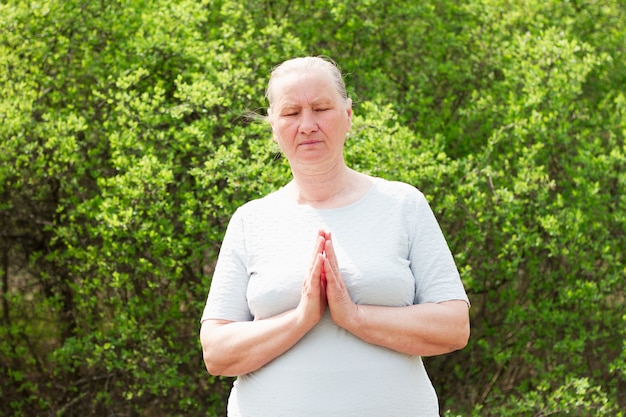 Mature woman meditates with folded arms.