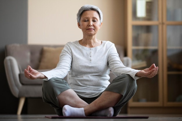 Mature woman meditating at home
