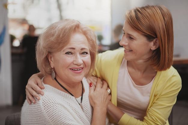 成熟した女性がコーヒーショップで彼女の年長の母親に会う