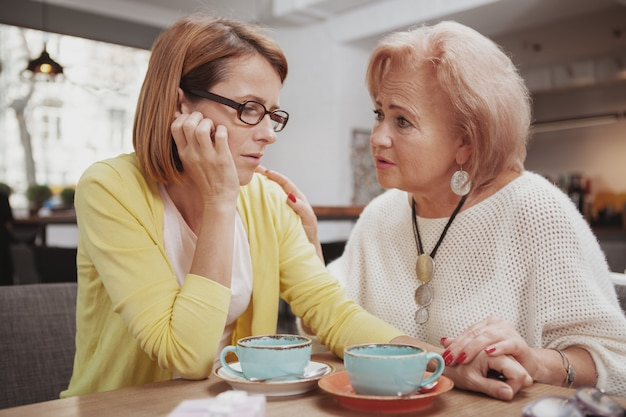 Mature woman meeting her senior mother at the coffee shop