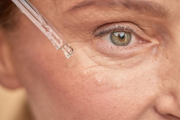 특별한 세럼으로 눈가 피부에 수분을 공급하는 중년 여성