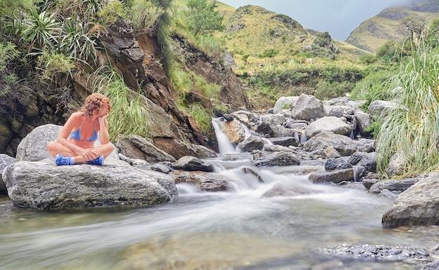 川の境界にある石の上で、植物と一緒に休んで瞑想している成熟した女性