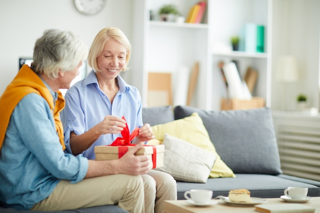 Mature woman opening birthday present