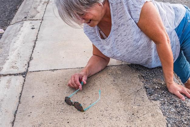 成熟した女性または高齢者が建物のゾーンを歩いていて、足を中に入れて大きな穴に落ちている-痛みを伴う地面での助けが必要