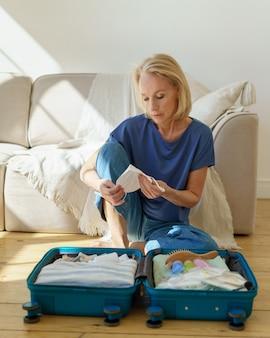 Зрелая женщина упаковывает чемодан, готовясь к путешествию во время пандемии