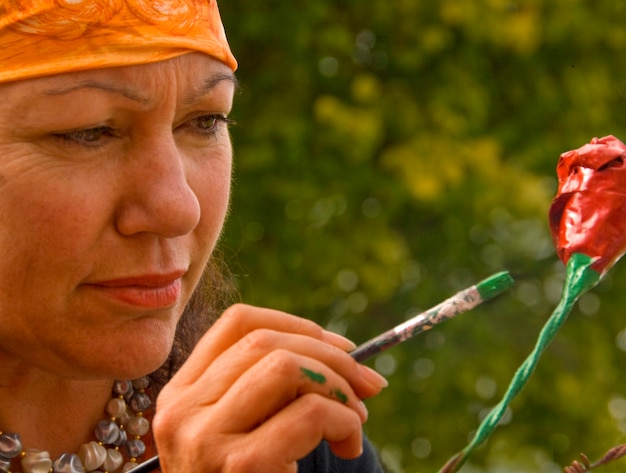 Mature woman painting flower, close-up