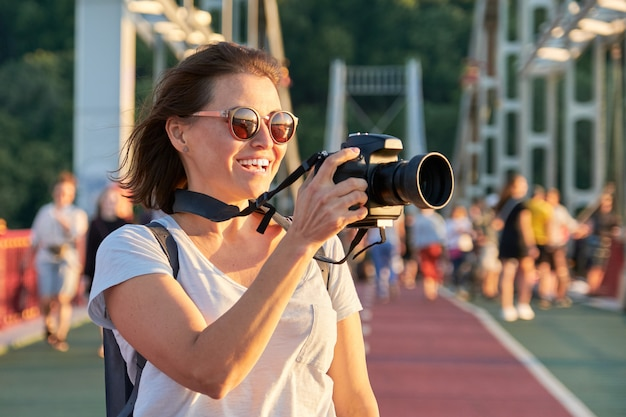 Mature woman photographer with camera taking photo picture
