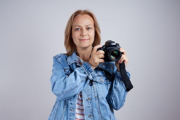 회색 배경에 전문 사진 카메라가 있는 성숙한 여성 사진사