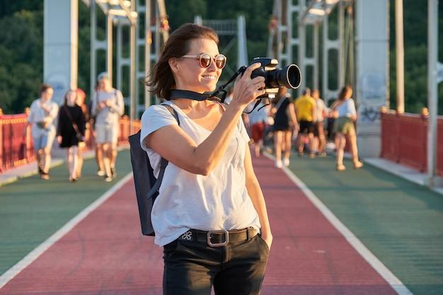 카메라로 촬영하는 성숙한여 인. 여성 사진 기자, 여행 블로거, 중년 여성 취미 사진