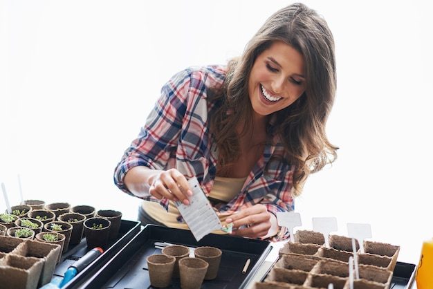 Mature woman planting seeds in greenhouse