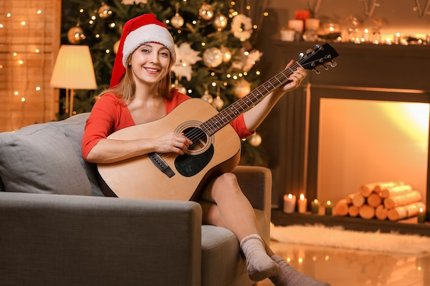 Зрелая женщина играет на гитаре дома в канун рождества