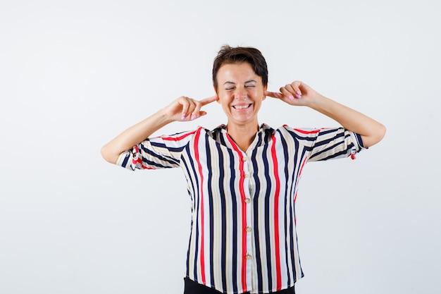 Donna matura che collega le orecchie con il dito indice mentre chiude gli occhi in camicia a righe e sembra felice, vista frontale.