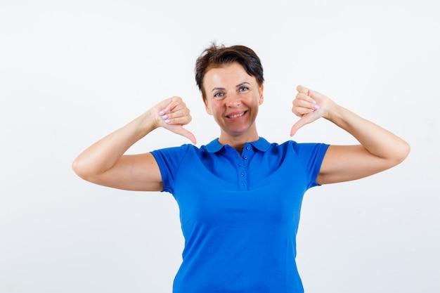 青いtシャツの親指で自分自身を指して、誇らしげに見える成熟した女性。正面図。