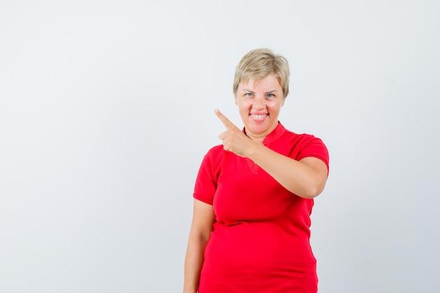 빨간 티셔츠에 왼쪽 상단 모서리를 가리키고 기뻐 보이는 성숙한 여자.