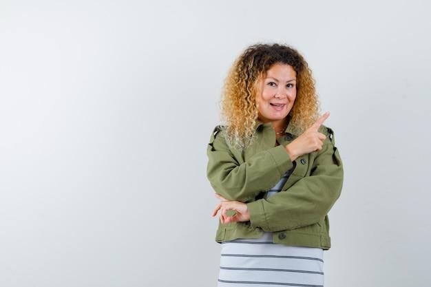 緑のジャケット、tシャツで右上隅を指して、陽気に見える成熟した女性。正面図。