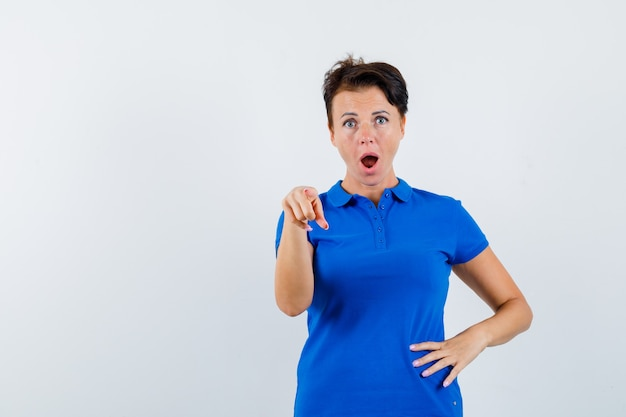 Mature woman pointing at camera in blue t-shirt and looking surprised. front view.