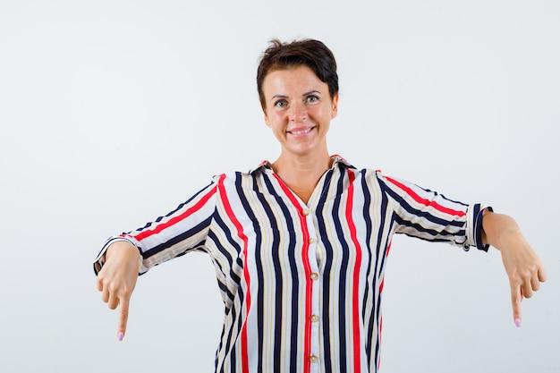 ストライプのシャツに人差し指で下を向いて幸せそうに見える成熟した女性、正面図。