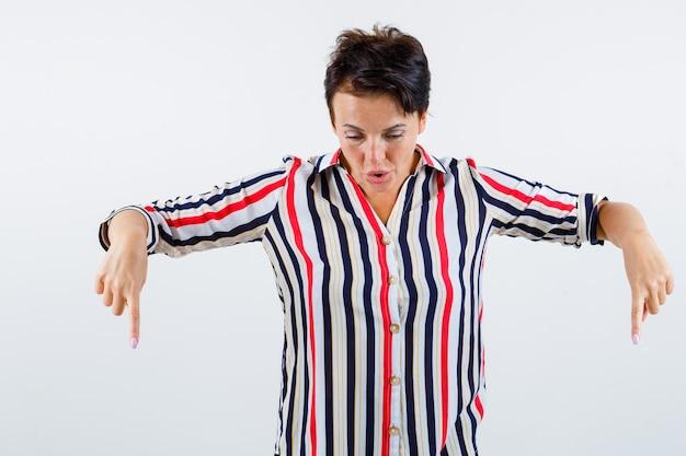 縞模様のシャツに人差し指で下を向いて驚いた様子の成熟した女性、正面図。