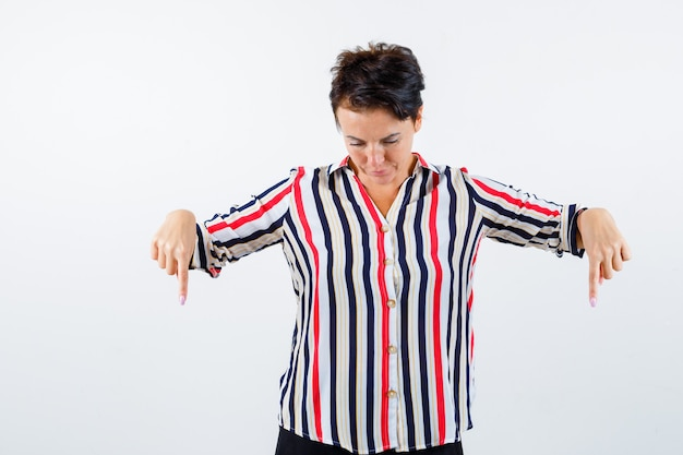 人差し指で下を向いている成熟した女性、縞模様のシャツで見下ろし、焦点を当てて、正面図。