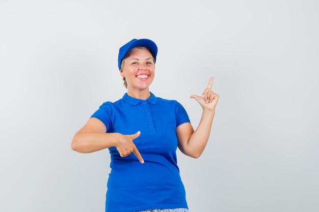 青いtシャツで指を上下に指して、うれしそうに見える成熟した女性。