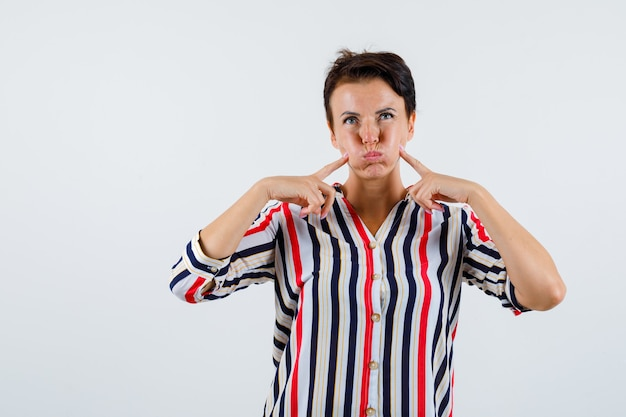 縞模様のシャツで頬を吹いて、面白がって見える、正面図に人差し指を指している成熟した女性。