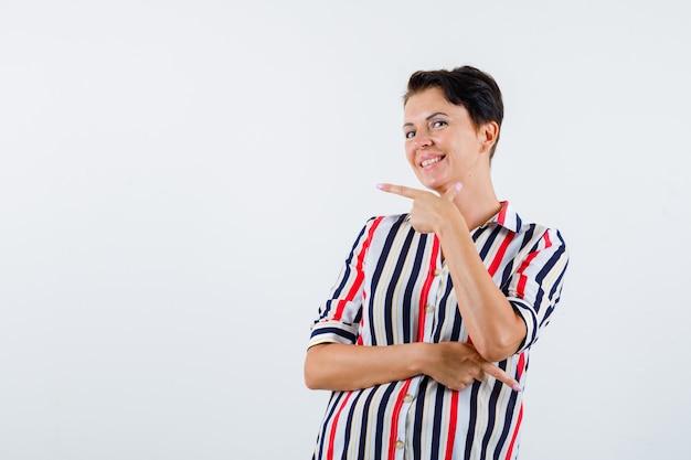 Donna matura che punta a sinistra ea destra con il dito indice in camicetta a righe e sembra allegra. vista frontale.