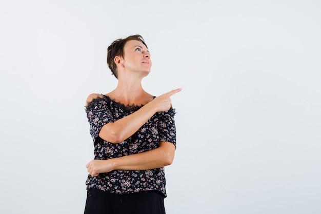 Donna matura che punta a destra con il dito indice in camicetta floreale e gonna nera e sembra seria, vista frontale.