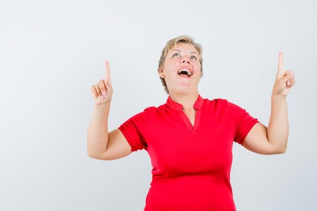 赤いtシャツを着て、幸せそうに見える成熟した女性。