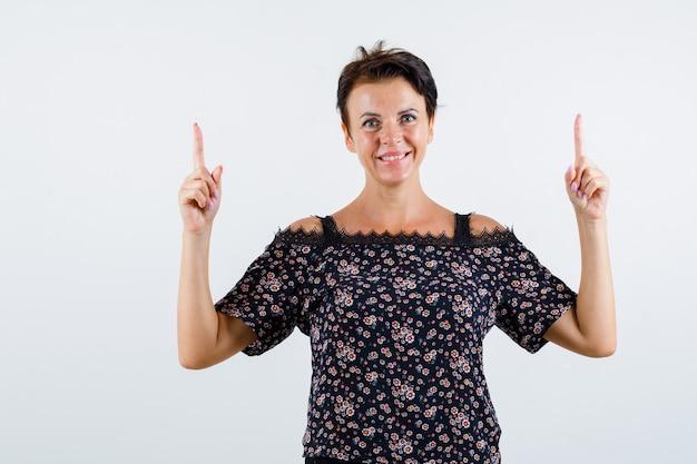 Donna matura rivolta verso l'alto con il dito indice in camicetta floreale, gonna nera e felice, vista frontale.