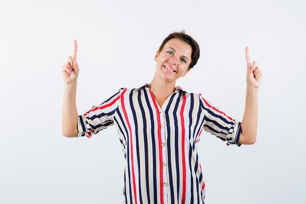 縞模様のシャツに人差し指で上向きに、陽気に見える成熟した女性、正面図。