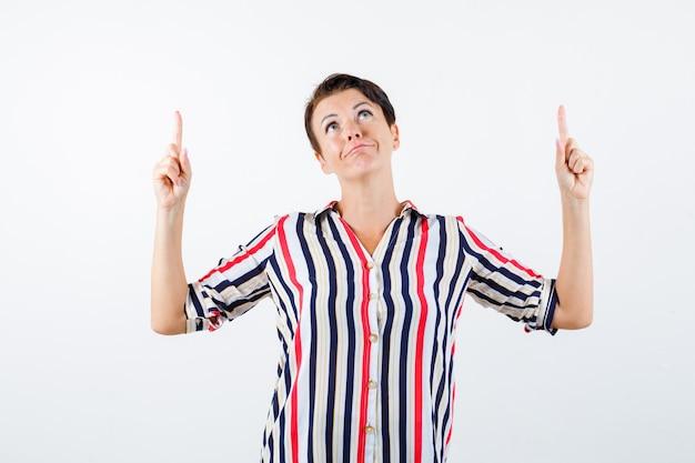 人差し指で上向き、縞模様のシャツで上向き、陽気に見える成熟した女性、正面図。