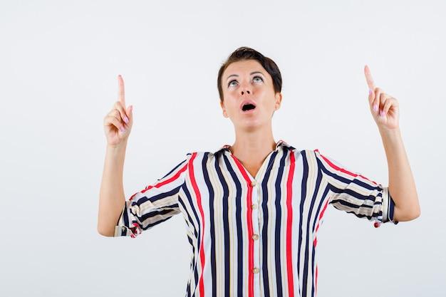 검지 손가락으로 가리키는 성숙한 여자 스트라이프 셔츠를 위쪽으로 찾고 초점을 맞춘, 전면보기.
