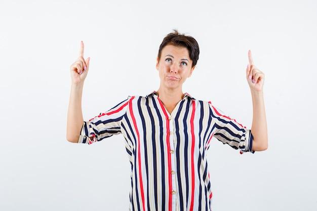 人差し指で上向き、縞模様のシャツで上向きに、焦点を当てて、正面図を見て成熟した女性。
