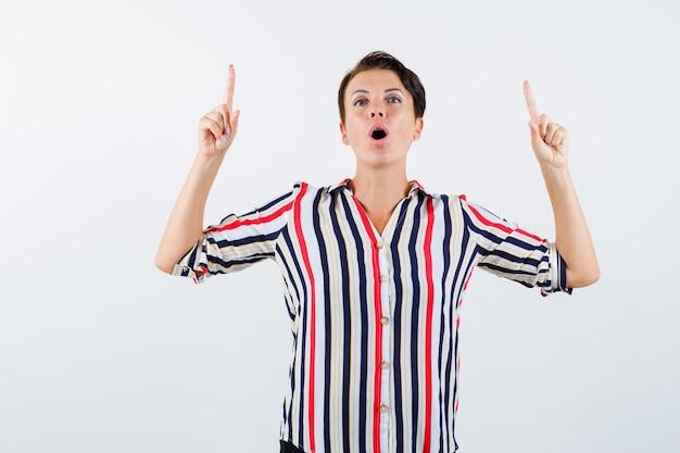 人差し指で上を向いて、縞模様のシャツを着て、驚いて、正面から見ている成熟した女性。