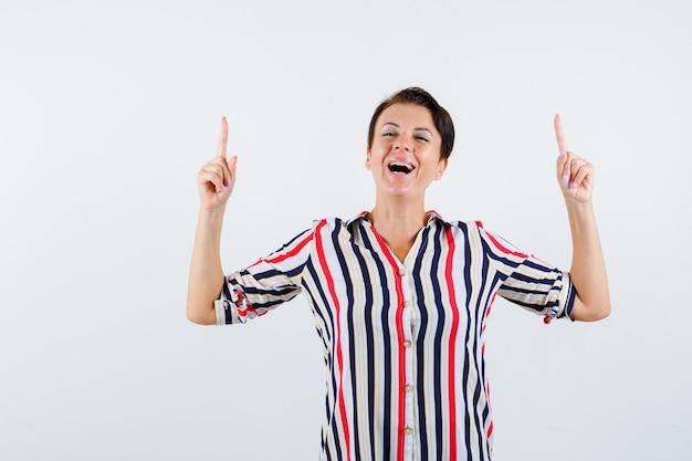 縞模様のシャツで目を閉じて幸せそうに見える人差し指で上向きの成熟した女性。正面図。