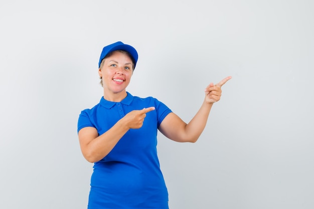 Mature woman pointing at upper right corner in blue t-shirt and looking jolly