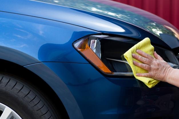 マイクロファイバーの布の車の詳細と自動車サービスの概念で車体を磨く成熟した女性
