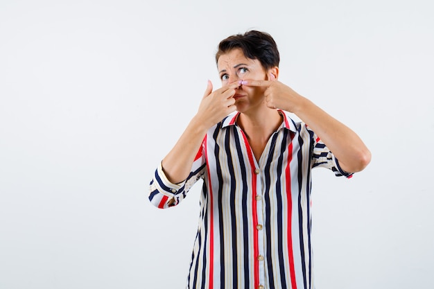 Donna matura schioccando un brufolo in camicetta a righe e guardando concentrato, vista frontale.