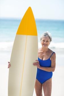 Зрелая женщина позирует с доской для серфинга
