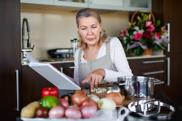 Mature woman preparing food in kitchen and looking at recipe book
