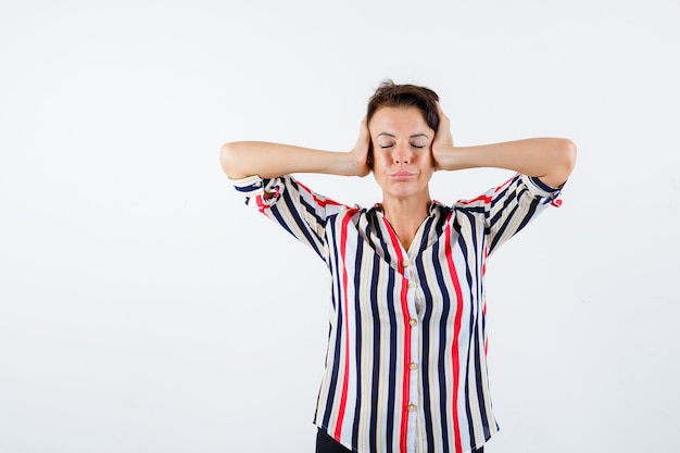 耳に手を押して、縞模様のシャツで目を閉じて、落ち着いて見える成熟した女性、正面図。
