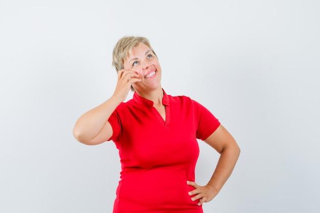 Donna matura che finge di parlare al cellulare in maglietta rossa e che sembra felice.