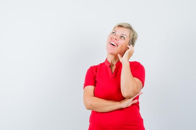 Donna matura che finge di parlare al cellulare in maglietta rossa e sembra allegra