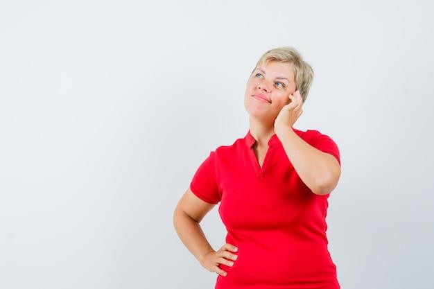 Donna matura che finge di parlare sul telefono cellulare in maglietta rossa e che sembra pensieroso